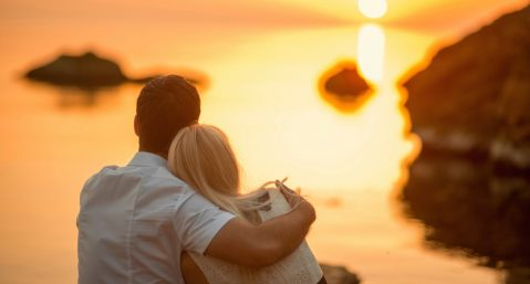 Couple watching sunset over water