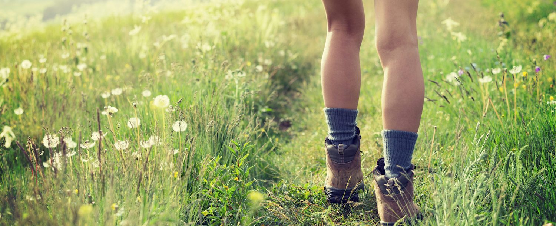 Woman hiking through grassland.