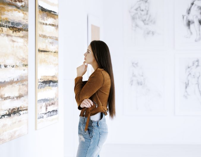 Young woman observing painting while visiting art gallery with famous artist collection