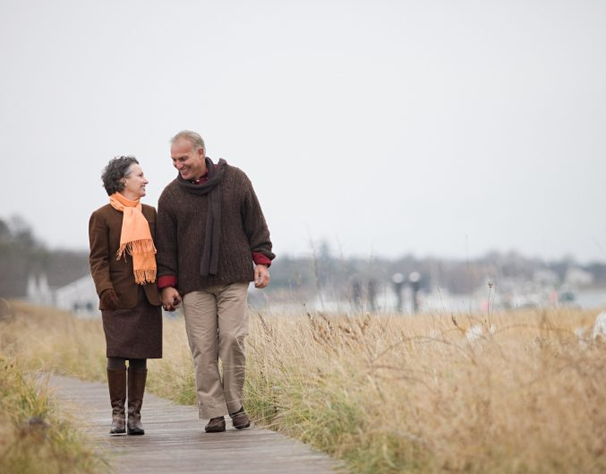 Couple walking next to a body of water in the fall.