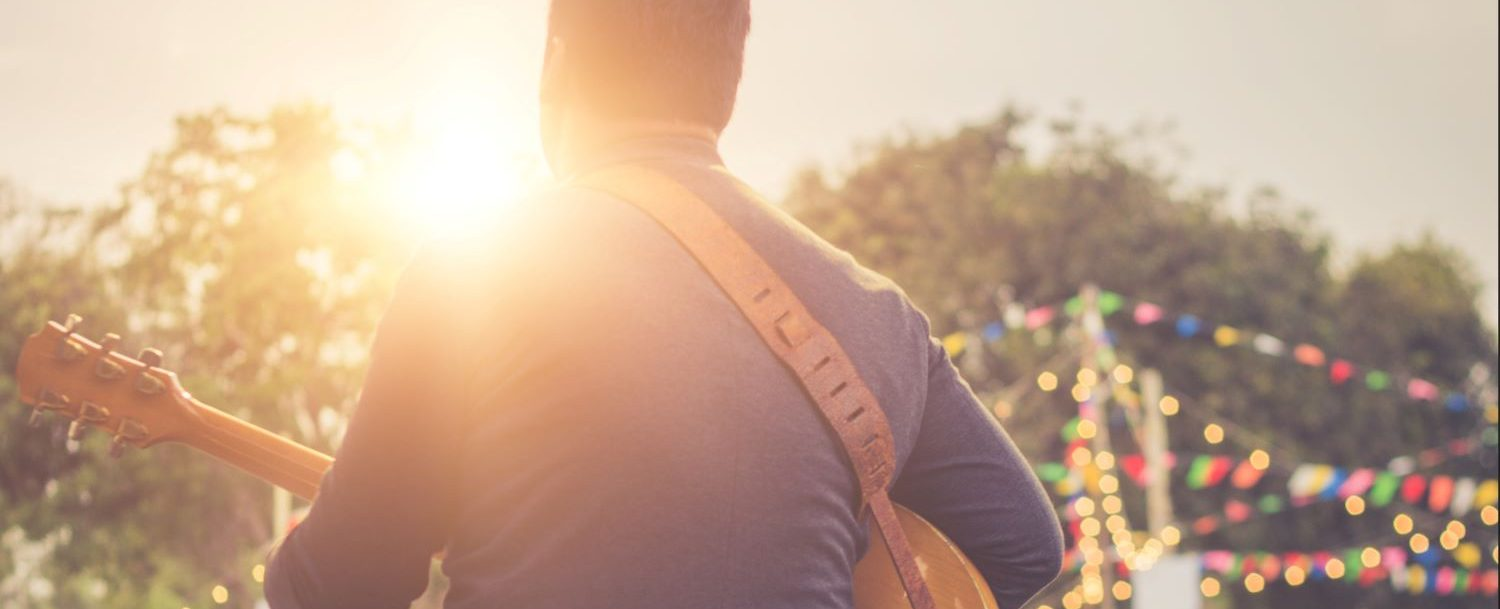 Guy playing guitar at an outdoor concert.